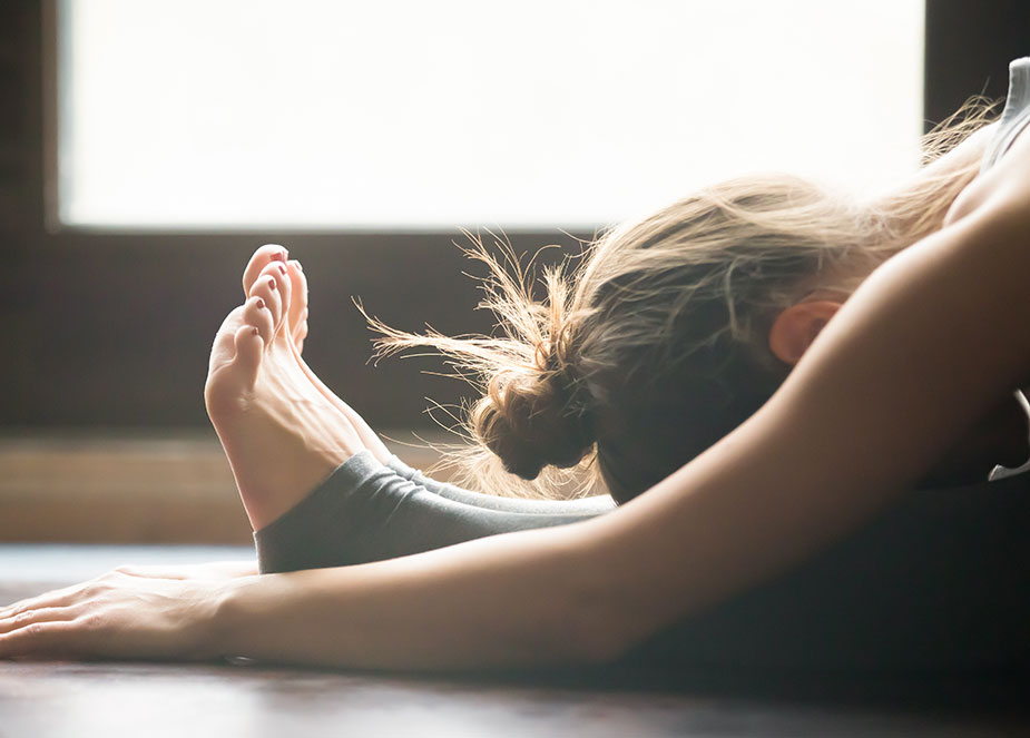 Young woman in drug rehab for opioid addiction stretching after yoga class.