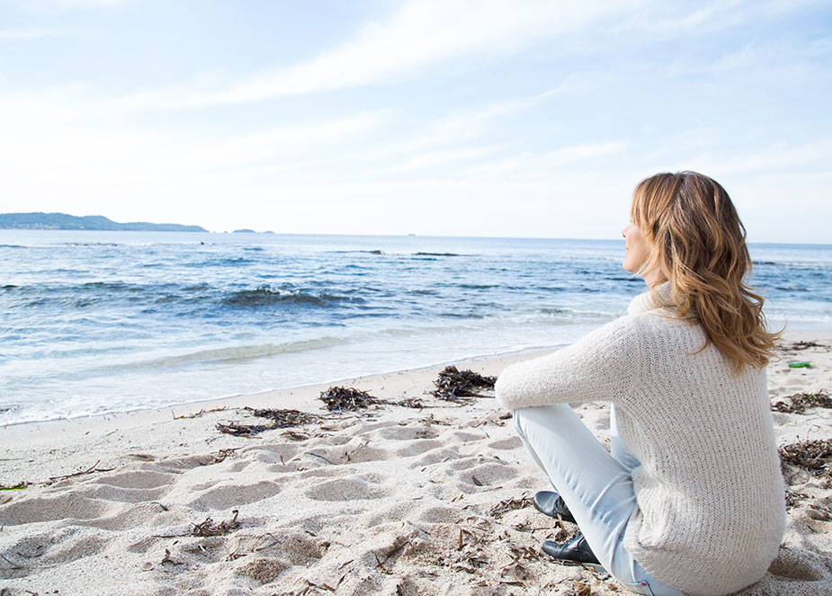 Young woman sitting on the beach, finding some peace and quiet during opioid addiction treatment.
